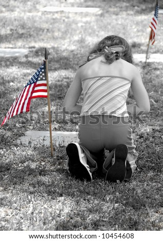 Young Child Paying Respect at Grave - stock photo