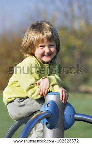 young child playing on colorful playground in a park - stock photo