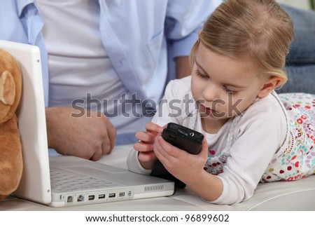 Young child playing with her father's mobile phone - stock photo