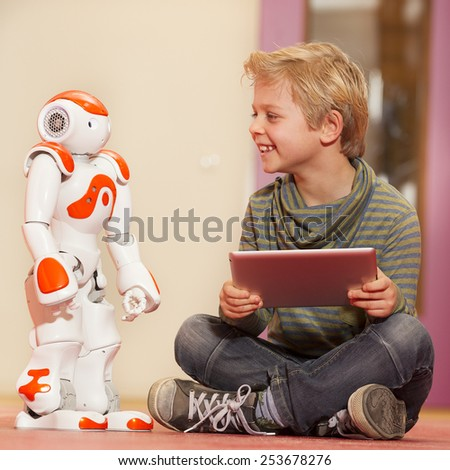 Young child playing with humanoid robot during school time - stock photo
