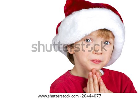 Young child praying for Christmas in a santa hat