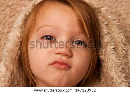Young child puckering lips under fur cover - stock photo