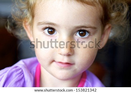 Young child/ toddler girl looking at camera. Big brown eyes. Head and shoulders. Facial expression.  - stock photo