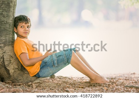 young child use a phone sit on a tree in a garden - stock photo