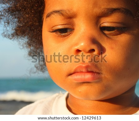 Young child with a sad facial expression - stock photo