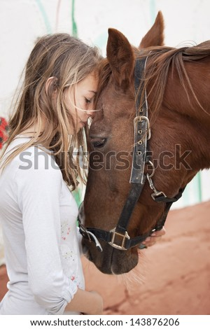 Young child with brown horse - stock photo