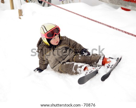 Young child with skis on sitting in snow - stock photo