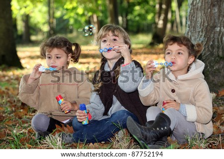 Young children blowing bubbles in the woods - stock photo