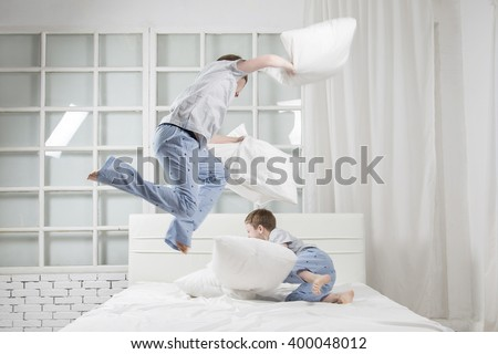 Young children playing on the bed. Pillow fight - stock photo