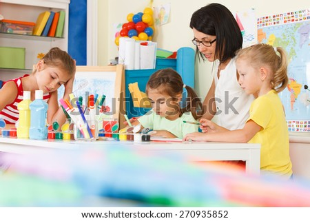young children with teacher draw in the classroom - stock photo