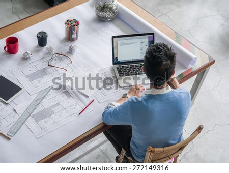 Young chineese engineer working in office - stock photo