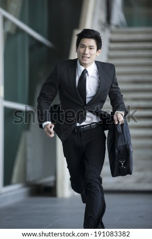 Young Chinese businessman running in urban setting
