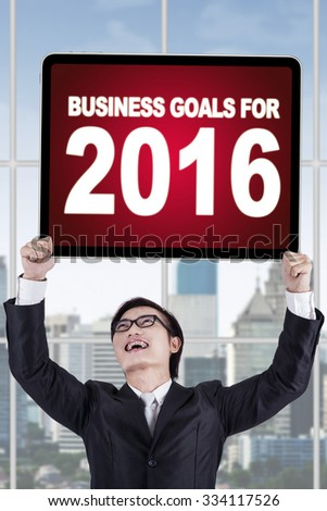 Young chinese businessman standing in the office while holding a board with a text of business goals for 2016 - stock photo