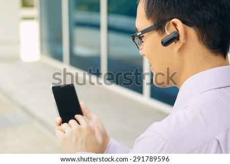 Young chinese businessman typing phone number on smartphone and talking with bluetooth headset device - stock photo