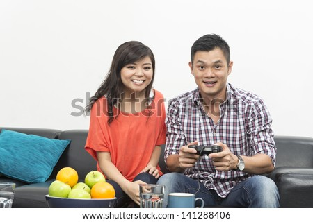Young Chinese couple playing video games at home together - stock photo