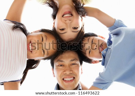 Young Chinese Family Looking Down Into Camera - stock photo