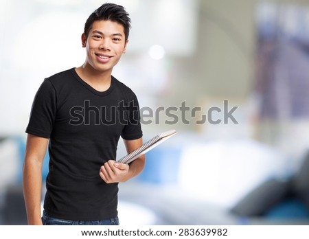 young chinese man holding his notebook