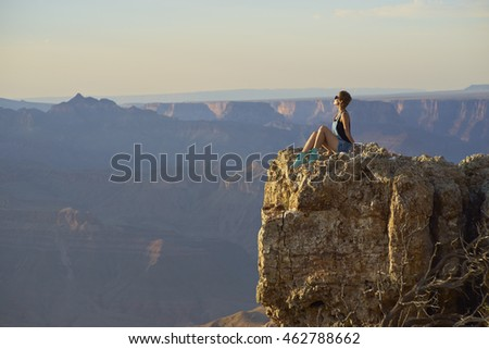 young Chinese woman sitting on cliff, Grand Canyon