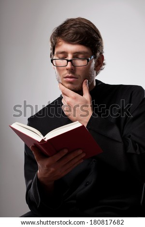Young christian priest in glasses is reading - stock photo