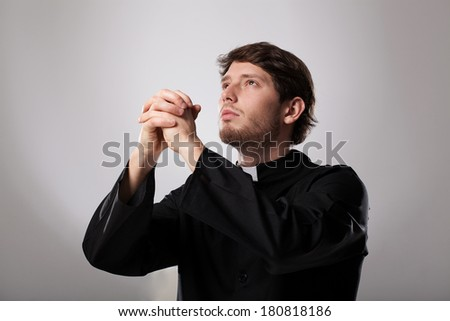 Young christian priest is earnestly praying to god - stock photo