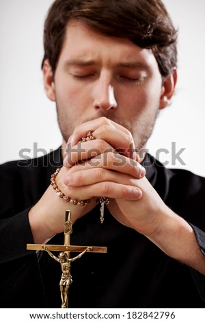 Young christian priest is praying the rosary - stock photo