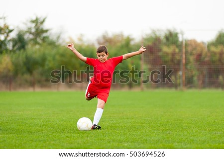 Young chubby soccer player kicking the ball