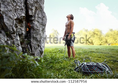 Young climber ready to conquer vertical wall with belay. Blue sky on the background