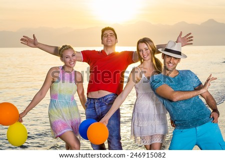 Young Close Friends in Random Happy Poses at the Beach During Sunset Time. - stock photo