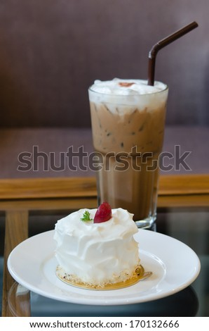 young coconut cake with fresh cream and red grape served with ice coffee