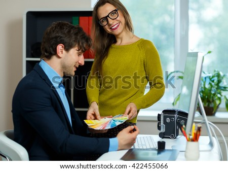 Young colleague - man and woman looking to a color paint palette at home office, modern business concept