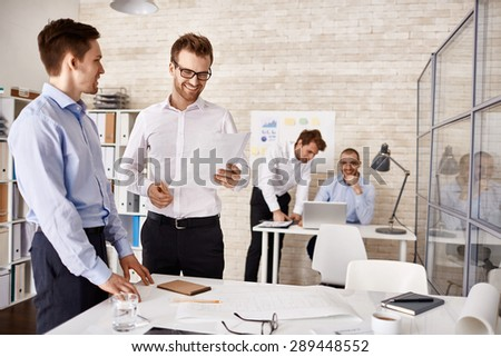 Young colleagues interacting at meeting in office - stock photo