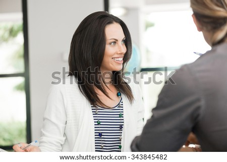 Young colleagues sitting at desk and having discussion in bright office - stock photo