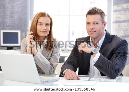 Young colleagues sitting at desk in bright office, working on laptop, smiling. - stock photo