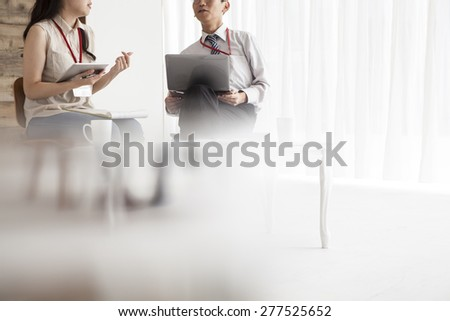 Young colleagues working in bright office - stock photo