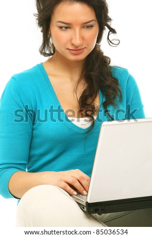 Young colledge girl sitting on the floor with a laptop, isolated on white - stock photo