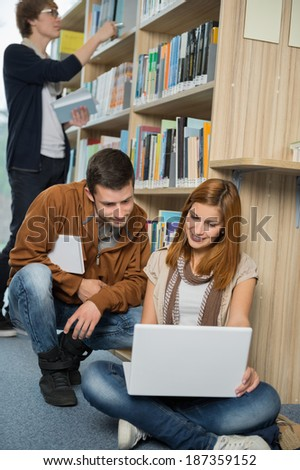 Young college friends studying together on laptop in library
