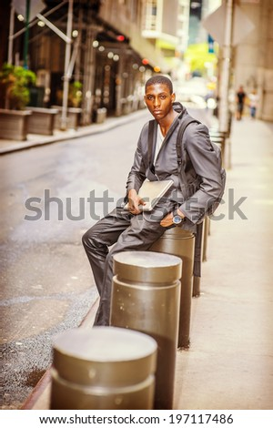 Young College Student. Carrying a bag, holding a laptop computer, a young handsome black guy is sitting on street, lost in thought. - stock photo