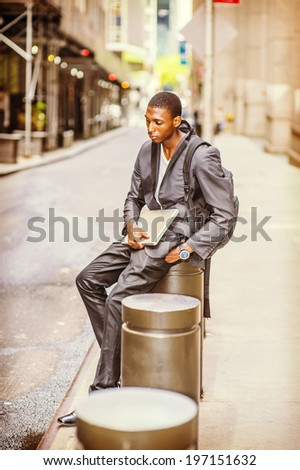 Young College Student. Carrying a bag, holding a laptop computer, a young handsome black guy is sitting on street, relaxing, waiting, thinking. - stock photo