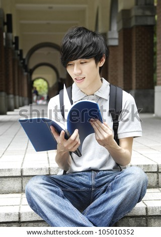 Young college student sitting student reading on campus