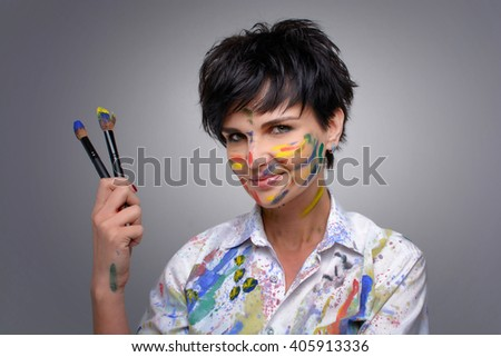 Young comedy, funny girl (architect, designer, web designer) with brushes in their hands smeared in colored paint posing and laughing in the studio in a white sports shirt - stock photo