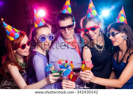 young company celebrates the holiday with cocktail in the hands - stock photo