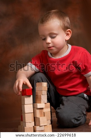 Young concentrated boy playing with wooden blocks - stock photo