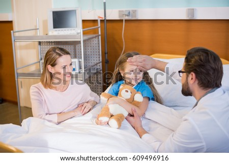 Young concerned woman watching doctor examining her daughter in hospital
