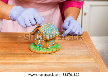 Young confectioner, wearing in pink apron and violet gloves, decorating gingerbread house with bag with white cream, on the wooden board, in the kitchen, close up