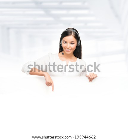 Young, confident and beautiful customer support operator with the blank billboard  - stock photo