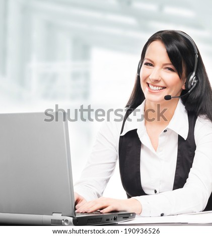 Young, confident and beautiful customer support operator working in a call center - stock photo