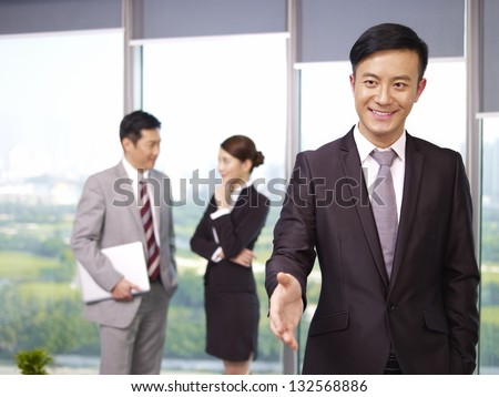 young confident asian business executive reaching out for a handshake. - stock photo