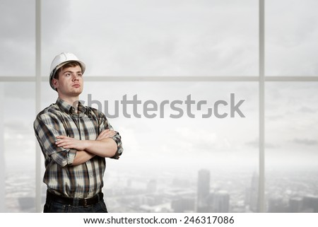 Young confident builder man with arms crossed on chest - stock photo