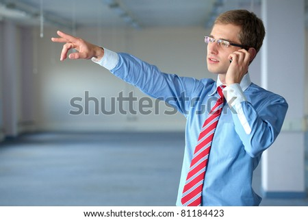 young confident businessman in blue shirt and red tie talks over mobile phone in his office - stock photo
