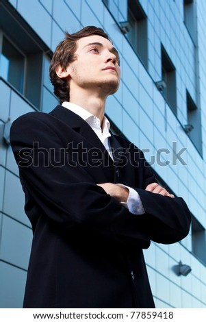Young confident businessman outside of an office looking to the future.